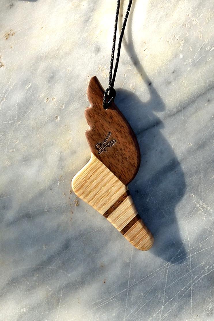 Χειροποίητο αρχαιοελληνικό κολιέ dion&felle, φτιαγμένο από συνδυασμό φυσικών ξύλων καρυδιάς και φράξου, από τη συλλογή Idέa. Το φτεροτό σανδάλι το θεού Ερμή.